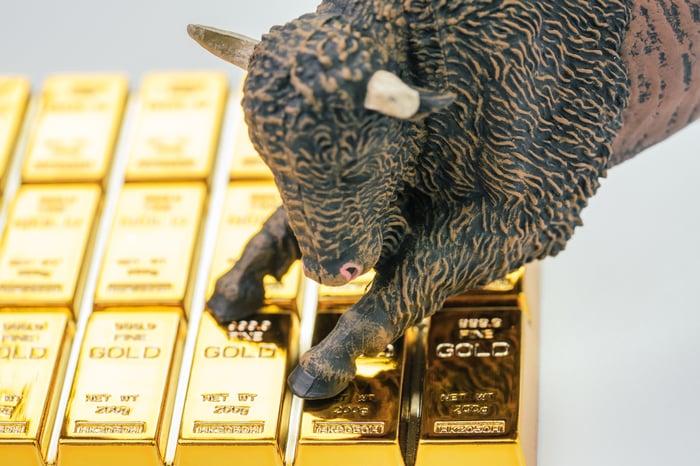 Bull jumping onto gold bullion bars.