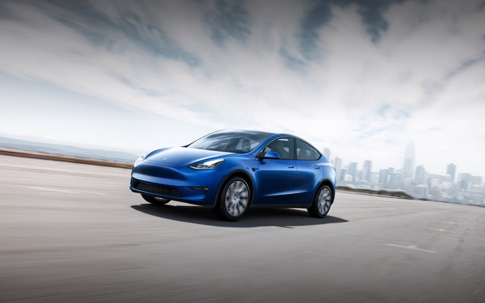 A blue Tesla Model Y in a large paved lot, with a city skyline in the background