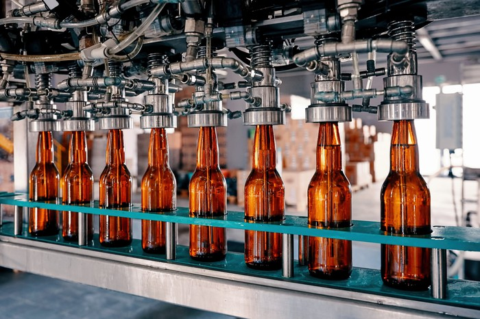 Beer bottling on a conveyer under a machine.