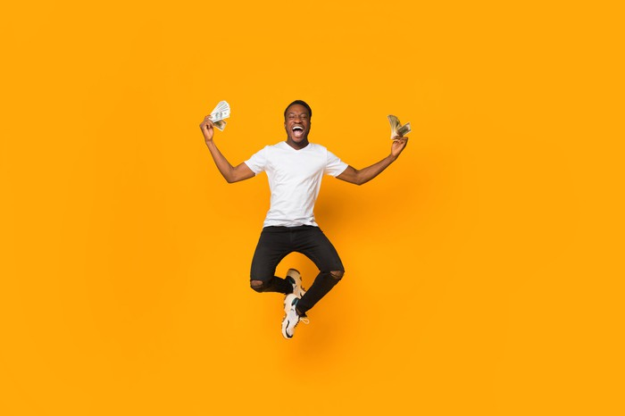 Excited man jumping while holding cash in hand