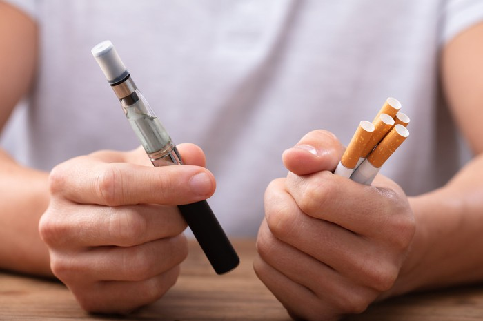 A man holds an e-cigarette and a bundle of cigarettes.