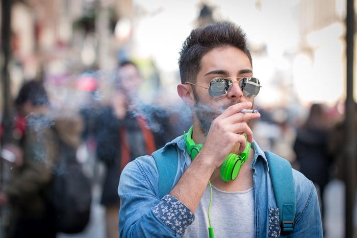 A young man smokes a cigarette.