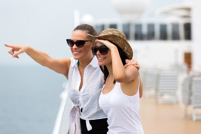 Two friends stand on a cruise ship's deck and smile as they point to something in the distance.
