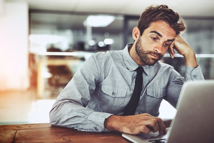 Man with bored expression sits at a laptop