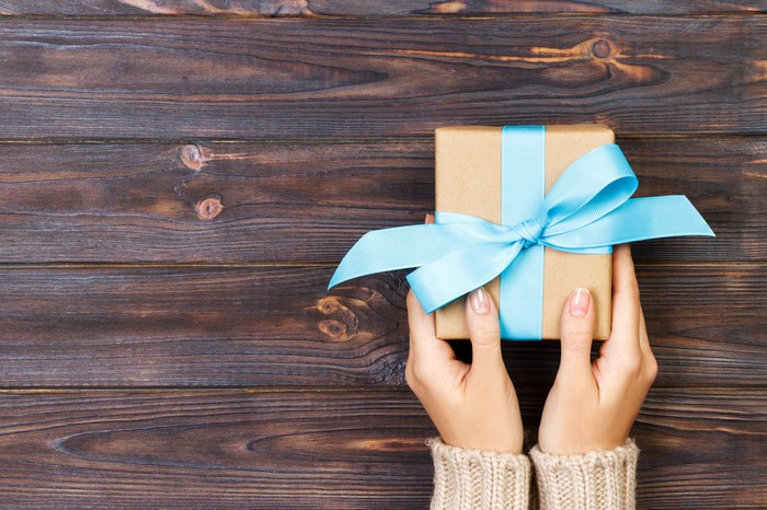 Hands holding small box with blue ribbon on a wood table.