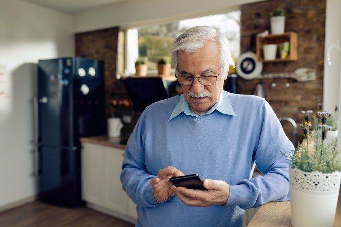 Older man holding mobile phone while standing in the kitchen.