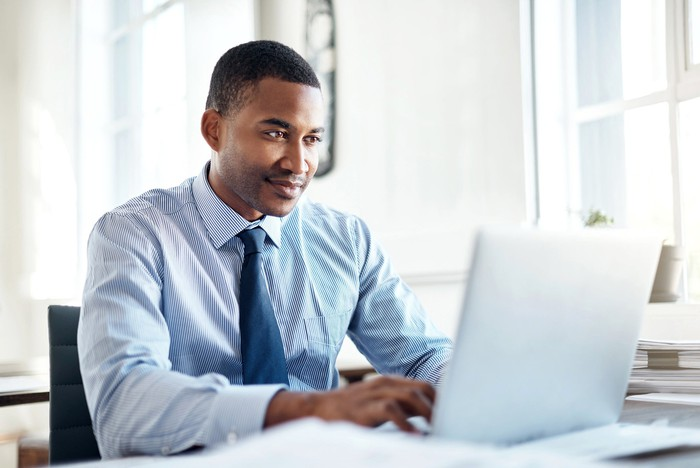 Man in dress shirt and tie typing on laptop