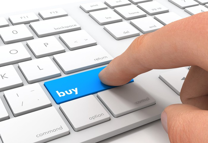 A person is pushing a keyboard button labeled buy.