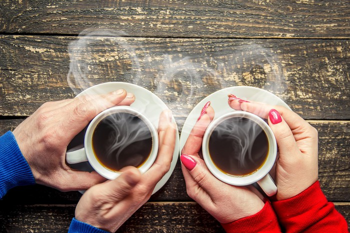 A man and woman holding two steaming hot cups of coffee.