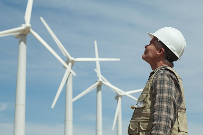 A worker stares up at several large wind turbines.