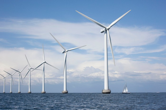 Seven wind turbines offshore with a sailboat for scale.