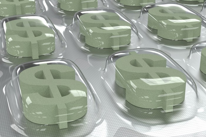 Prescription drug packaging containing green dollar signs where capsules would usually be.
