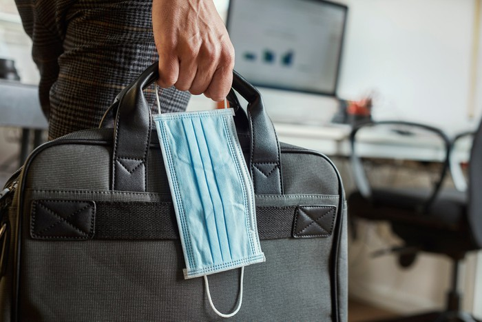 A worker holds a suitcase and a medical mask.
