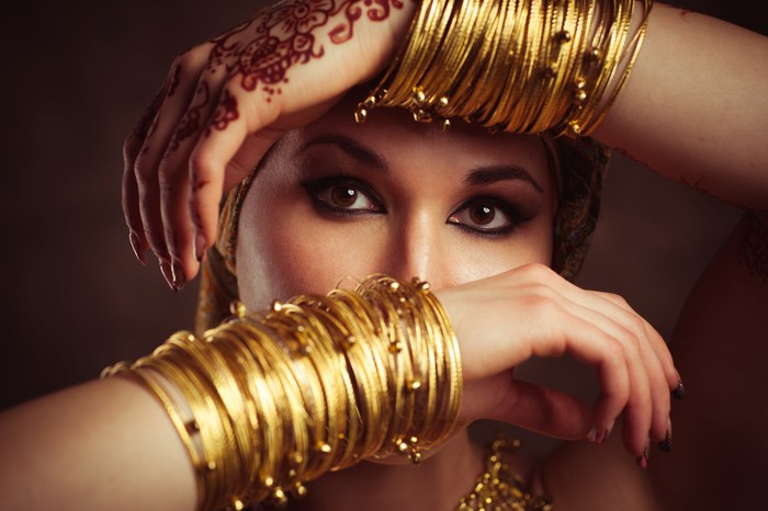 A woman holding up her arms that are adorned with gold bangles.