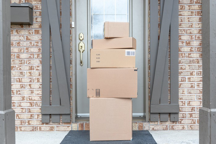 Multiple packages sitting on a doorstep.