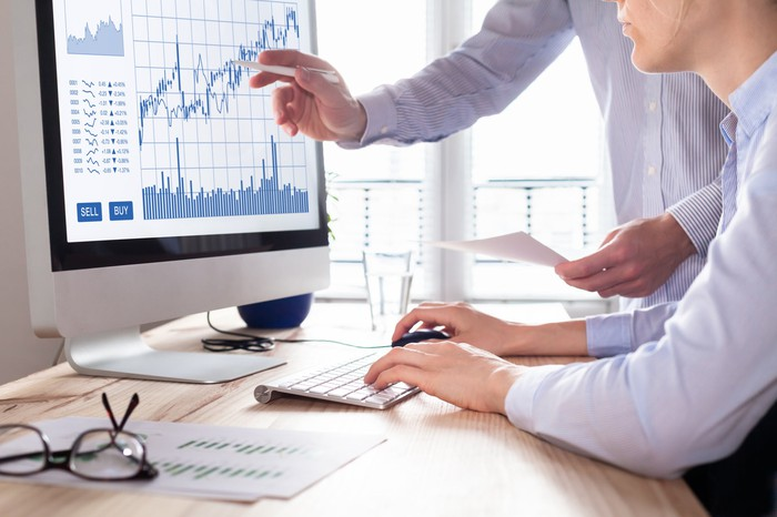 Businessman pointing to financial chart on monitor.