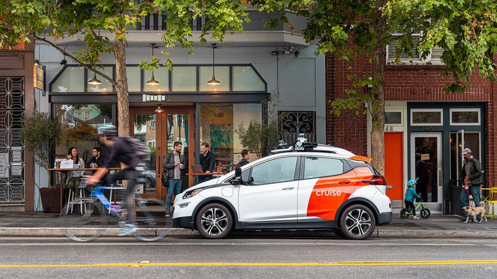 A Chevrolet Bolt EV with Cruise emblems and self-driving sensor hardware, on a San Francisco street.