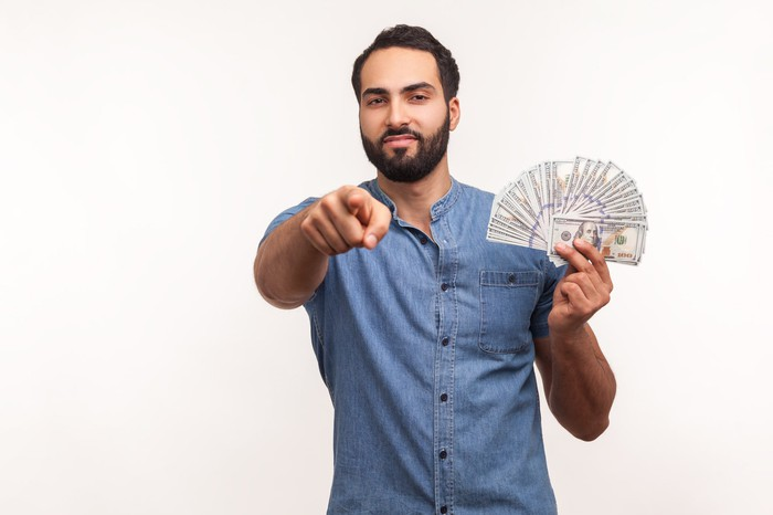 A man holding bills fanned out in one hand and pointing straight ahead with the other.
