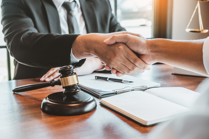 Two lawyers shaking hands over a desk with a gavel and scales in the background