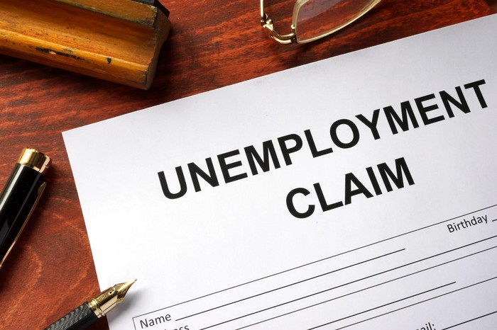 Paper labeled Unemployment Claim on a wood desk with a pen and glasses.