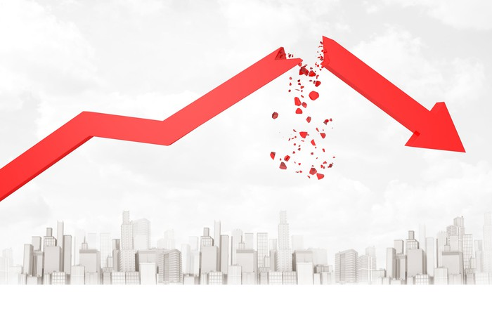Red stock arrow breaking up and showering down in pieces over a city below