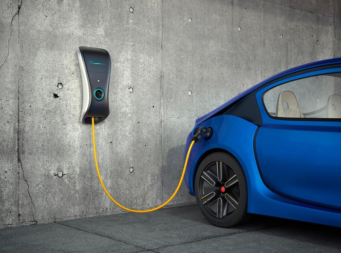 Blue car plugged into a charger on a concrete wall.