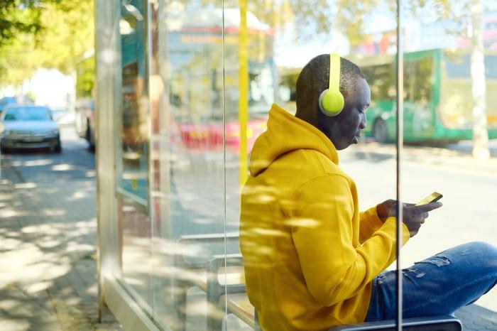 Man sitting at bus stop wearing headphones
