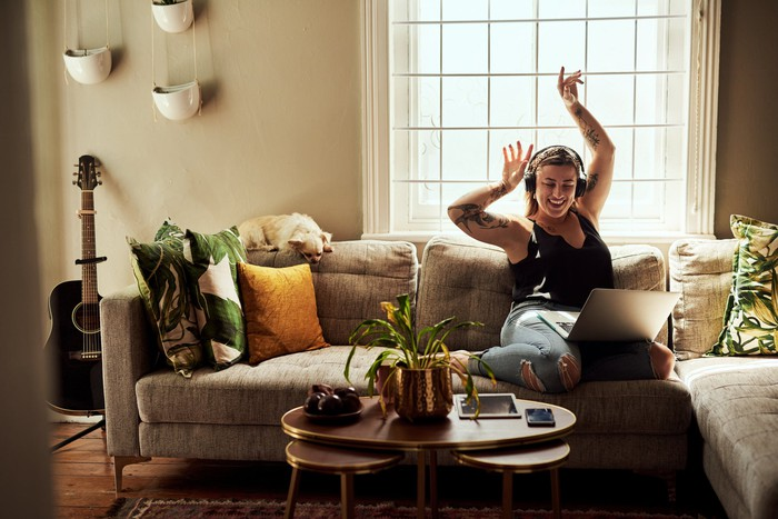 Woman listening to headphones on her couch and raising her arms