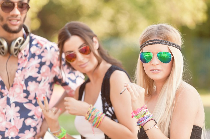Young people are in sunglasses smoke from the pot on a sunny day.