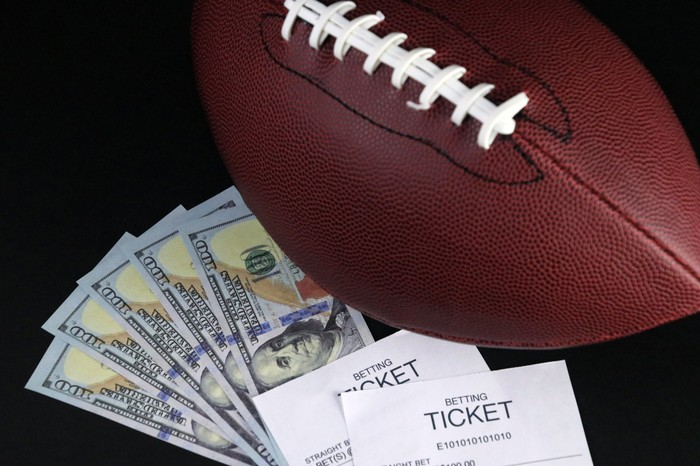football with betting ticket and $100 bills