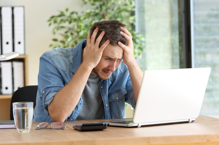 A frustrated man places his hands on his head while staring at his laptop screen.