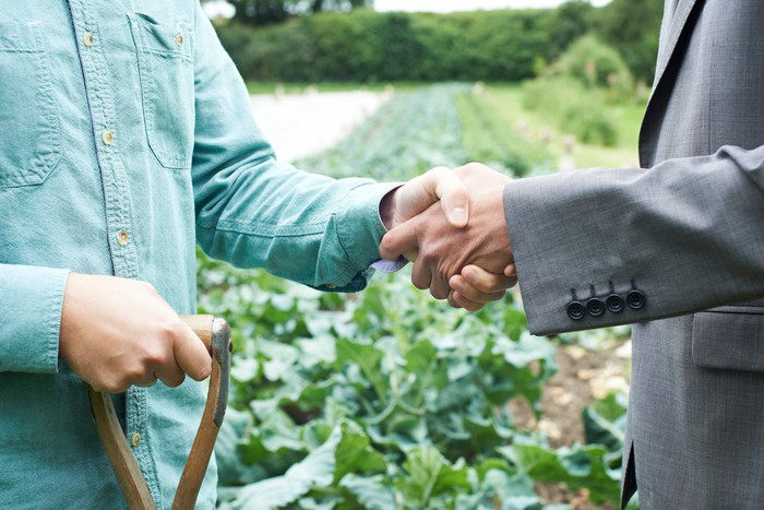 Close-up of a farmer and a banker shaking hands in a field.