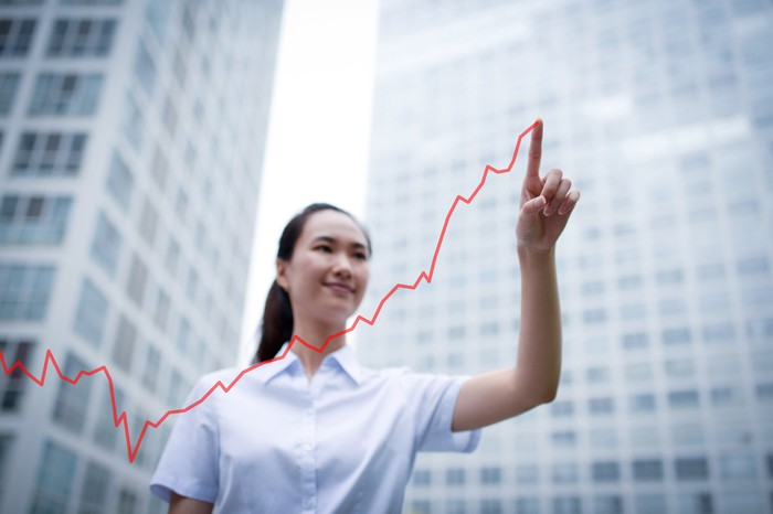 An investor, standing in front of skyscrapers, draws a red line in the air with her finger to indicate a stock rising.