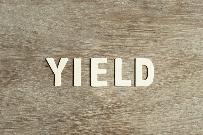 The word yield on a wooden background.