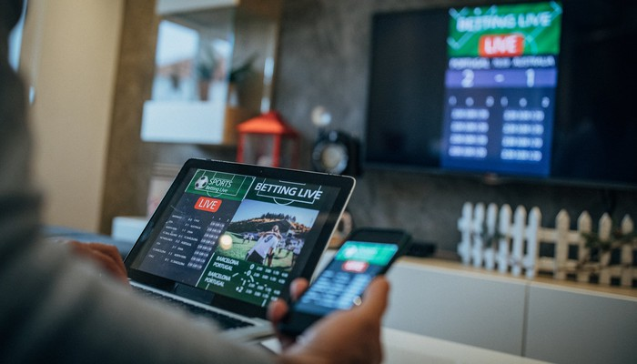Person betting on sports on multiple devices