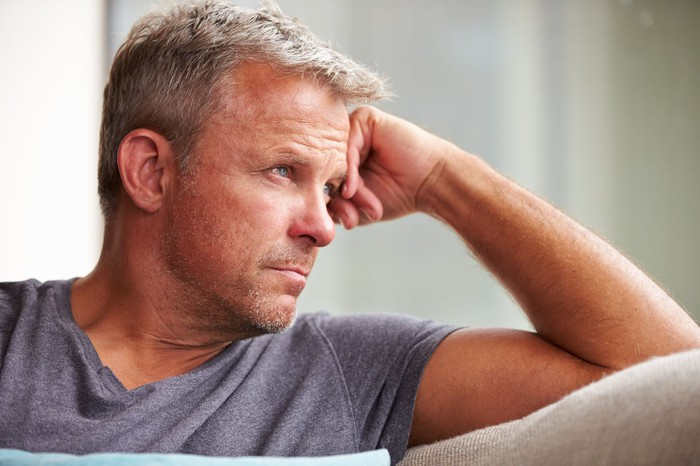 Mature man with a concerned expression on his face looking out the window.