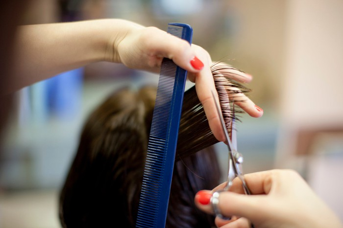 Close-up photo of a hairdresser cutting a customer's hair.