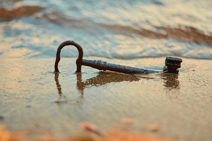 Rusty key in wet beach sand