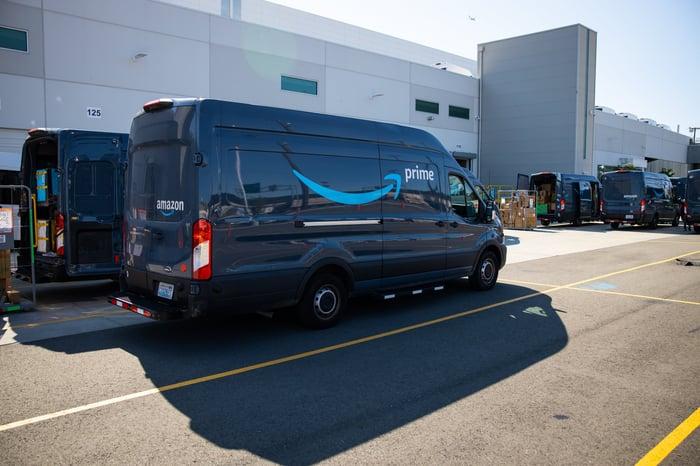 Amazon cargo vans near a warehouse loading dock.