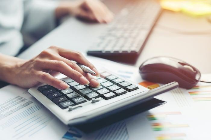 Woman using a calculator at a desk.
