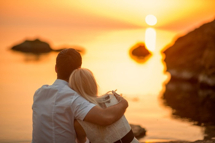 Couple looking out at a sunset on the ocean.