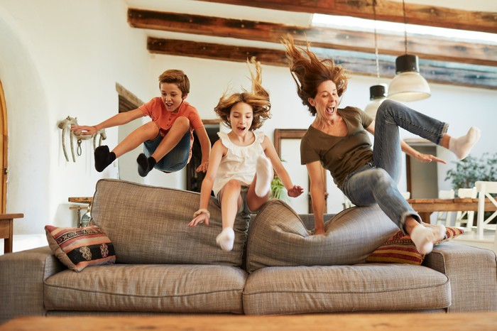 A family leaping over the back of a sofa.