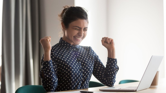 Woman celebrating at computer