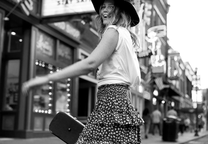 A young woman turns around on a downtown street.