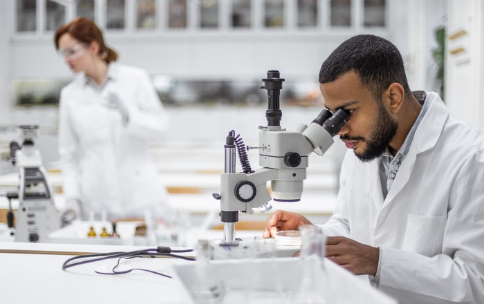 Two scientists in a lab with one looking through a microscope.