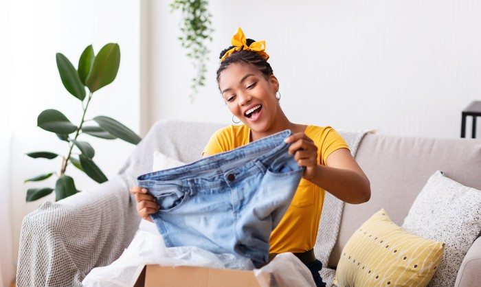 A woman opening a box of clothes.
