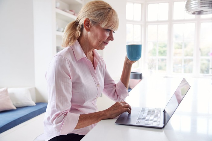 Older woman at laptop holding mug