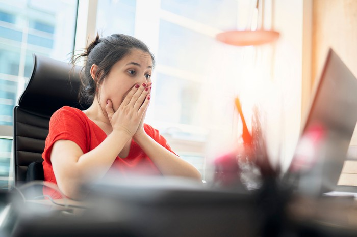A woman sitting at her computer with her hands over her mouth as if surprised.