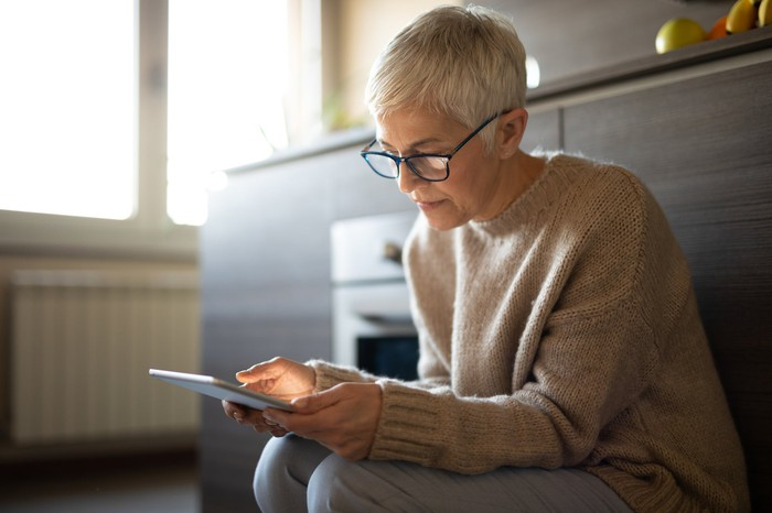 Seated older woman with serious expression holding tablet