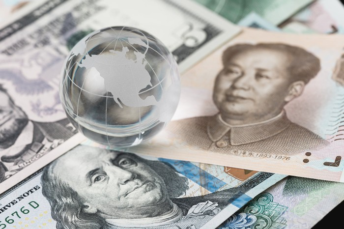 Paper currency from the U.S. and China, with a small shiny globe as a paperweight
